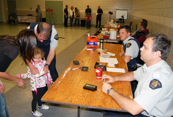 Auxiliary Constables Eric Scarcella and Joe Marcoffio watch as Carter finishes Ava Lund's fingerprints. And those were just the first part of the process. David F. Rooney photo