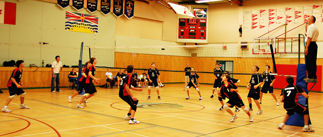 The Revelstoke and Okanagan Mission appear in motion as they wait to see where the volleyball will come down during their championship game on Saturday. David F. Rooney photo