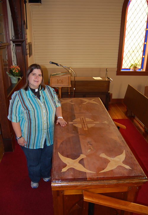 The new priest at St. Peter's Anglican Church, Rev., Heather Hamlin Gravells admires the inlaid wood decoration produced by Ken Sakamoto for the surface of the altar. Gravells and her family are struck by the welcoming nature of not just local parishioners but the community in general. David F. Rooney photo