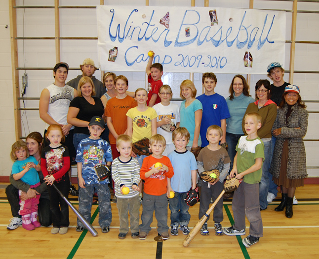 Revelstoke Minor Baseball's Lina Sihlis (far right) poses with coaches Jake Beech (just behind her) and Alex Sessa (far left, back row) and some of the parents and kids who came out for a Winter baseball Camp at the Mount Begbie Elementary School gym. The camp is ongoing. For more information please contact Sihlis at 250-837-4869. Sihlis and her family have for years been involved in and have sponsored local baseball for young kids. David F. Rooney photo
