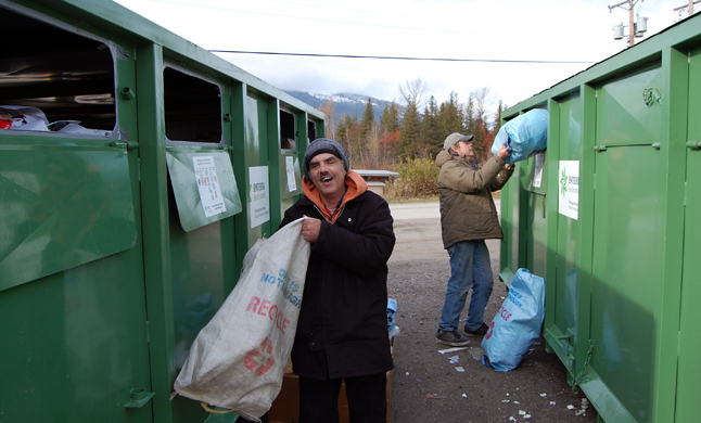 Chuck Ferguson (left) and Kevin Springall do a little recycling at the big green bins by the Forum Wednesday. They are just of the hundreds of people who regularly use the bins to recycle their household plastics, paper, glass and metal containers. David F. Rooney