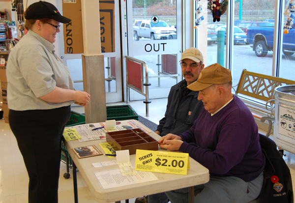 Sheryl Anderson (left) was feeling lucky on Saturday so she sprang for a ticket in the Knights of Columbus' annual vehicle lottery from Keith Burgart (center) and Ron Holloway. And why not? Two of the last three winners have been from Revelstoke.  David F. Rooney photo