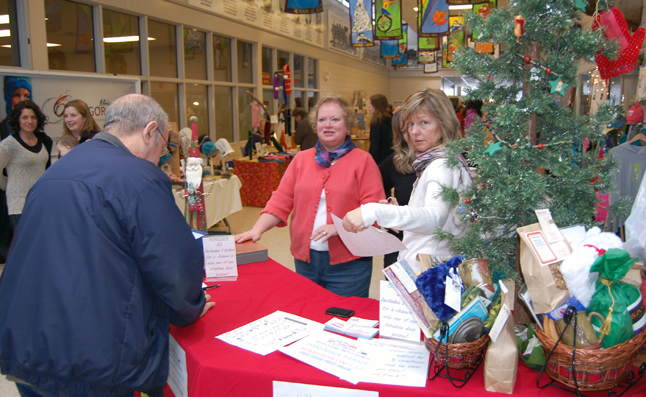 Cathy Granstrom (center) and Tina Lindegaard were the keepers of the gate for a while at the Handmade Parade's opening on Saturday. Hundreds of people roamed through the annual arts and crafts fair at the Community Centre searching for that perfect gift. David F. Rooney photo