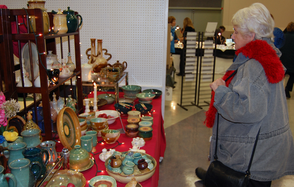 Bev Wiege considers the pottery option at the Handmade Parade. David F. Rooney photo