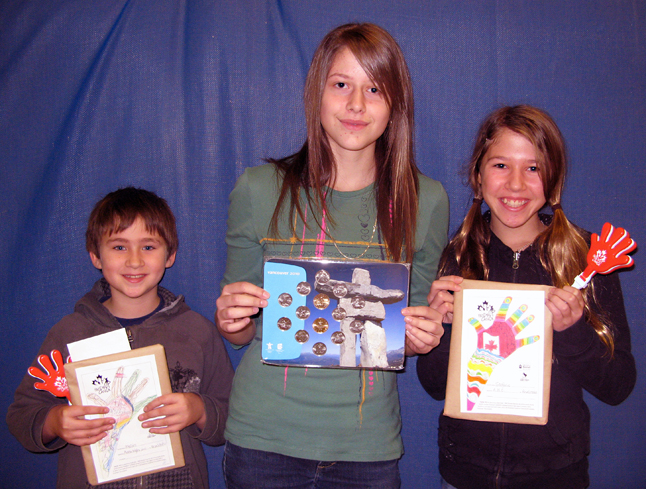 """Arrow Heights students Brandon Lavers of Grade Three (left), Shayna Seyl of Grade Seven and Stephanie Wallach, also of Grade Seven, pose with their award-winning pictures of coloured hands. They were among the local students who submitted 138 coloured hand pictures that were sponsored by generous shoppers at $2 a pop. The $276 they raised goes to help our Paralympic Athletes train for the 2010 Olympics. Over $13,000 has been raised across Canada so far.  According to AHE teacher Laurel Russell """"from the decorated hands submitted by schools throughout Canada, 18 were selected as prize winners. I am thrilled to tell you that three of those students honoured are from our school!""""  Each student received an Olympic Coin Set, an Olympic Pin, a handclapper noisemaker and a letter of recognition.  Photo courtesy of Laurel Russell"""