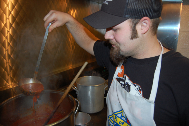 Derek Burgart inspects the savoury sauce that for the Knights' meal. David F. Rooney photo