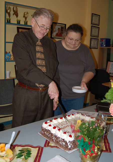 Peter Waters cuts the cake at the Revelstoke Awareness and Outreach Program's Fourth Anniversary Party Thursdy as Linda Streeter waits for a slice. David F. Rooney photo