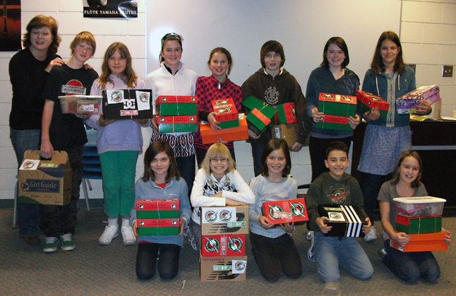 AHE Student Council members proudly display the 27 boxes of items collected during their Operation Christmas Child campaign.  Parent Noelene Mostert (left) provided her expertise and guidance in assisting students as they filled the boxes with a variety of personal items including toiletries, clothing, school supplies and toys.  Photo courtesy of Arrow Heights Elementary School