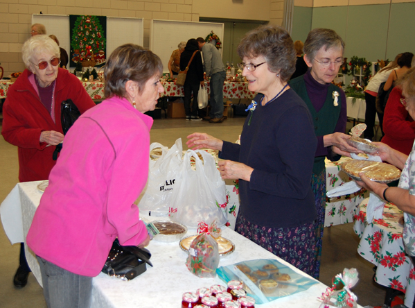 Miriam Williams (center) makes a sale at the baked goods table at this year's United Church Women's Bazaar and Baker Sale at the Community Centre on Saturday.  David F. Rooney photo