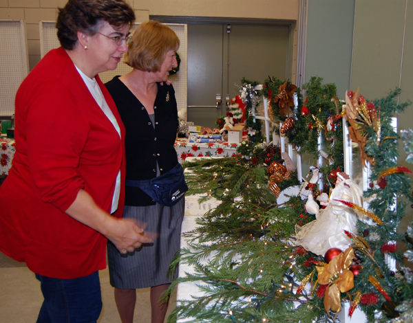 Wendy Lucas (left) examines some of the Christmas Windows that Judy Barrett was offering to ornament-hungry shoppers.  David F. Rooney photo