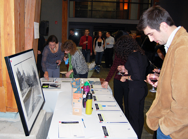 A patron considers his choices at the silent auction, which included a ski lift chair, three prints by Rob Buchanan, gift baskets of wine and other highly desirable items.  David F. Rooney photo