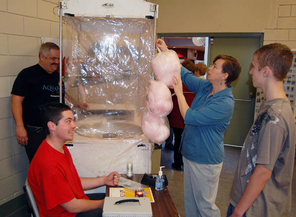 Mcpl. Dustin Andrew (center, left in red) and Cpl. Tyler Coley (right) had a sweet job fronting for the cotton candy being whipped up by Rocky Mountain Rangers Capt. Kelly Rienks and hung out for display by Suzanne Tippe. David F. Rooney photo