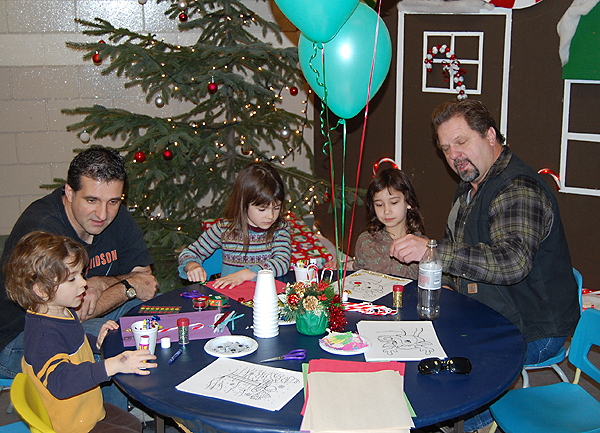 Wally Veninsky (left) and Bob Loeppky (right) have fun with their kids, Samantha, Zach and Mercedes at the kids' fun table. David F. Rooney photo