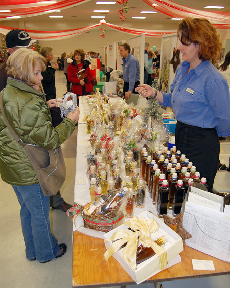 Elvira Brunner (right) of Crescendo tells a potential customer about the superior quality and variety of the oils and spices she and her partner Daniel Weber (center, right background) have on offer. David F. Rooney photo