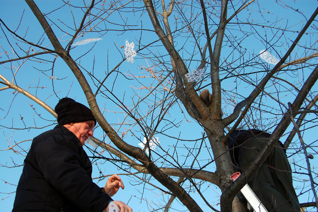 Holloway and Battersby hang the snowflakes. David F. Rooney photo