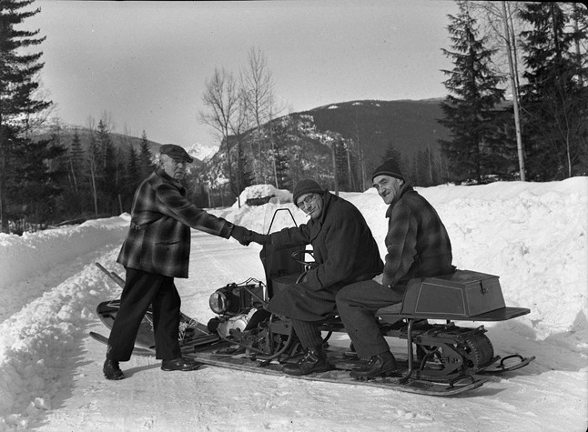 There's nothing really new about snowmobiling in Revelstoke, as you can certainly see from this old photo that illustrated an article headlined, Mechanized 'Dogs' Put Louie Ahead, in the Vancouver Sun on Saturday, Feb. 21, 1948.  Qualified approval of Louie Bergen's new motorized toboggan if given by Angus Beaton, old-time dog-team driver.  He is shown wishing Bergen luck at start of 100-mile trip over snow-swept Big Bend Highway to reach his auto camp at Boat Encampment, north of Revelstoke. Photo courtesy of the Revelstoke Museum & Archives