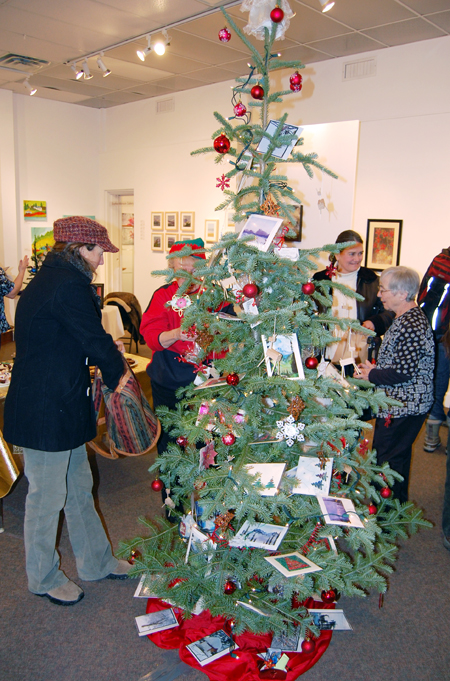 Jackie James (left) contemplates a purchase from the Christms Gift Tree at the Revelstoke Visual Arts Centre's Affordable Art Fair on Friday evening. Local artists have produced affordably priced paintings, sculptures, cards, photographs and other sensory delights to fit any pocketbook. The Fair runs until Dec. 20 and the gallery will be open every day until then from 1 pm until 5 pm. David F. Rooney photo