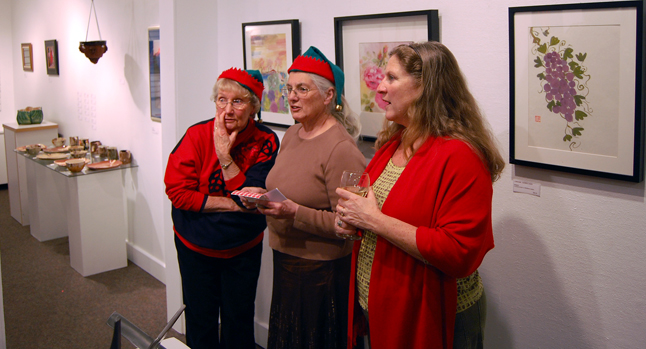 Pat Anderson (left) whispers to fellow artist Sandra Flood as Carol Palladino looks on at the Affordable Art Fair. Not only did Anderson and Flood have paintings and ceramics on offer, their festive head gear singles them out as official exibitors at the show. As for Palladino, she was no doubt shopping for the perfect gift for someone. David F. Rooney photo