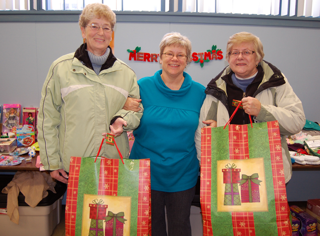 Judy Krywa (left) and Marian Peppler (right) of the Beta Sigma Phi sorority pose with Community Connections Food Bank Coordinator Patti Larson Friday as they dropped off a couple of large gift bags intended for the Food Bank's Christmas Hamper Program. David F. Rooney photo