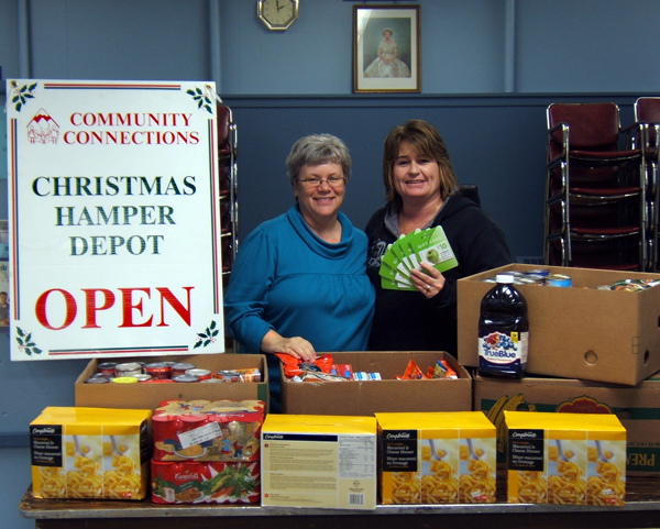 Patti Larson, Community Connections' outreach services manager and coordinator of the agency's Food Bank (left), accepts 300 lbs. of food and $370 in Cooper's food vouchers from the Revelstoke Snowmobile Club's Kathy Burke about two weeks ago. Burke said the club, which was again this year the first group to donate to the Food Bank's Christmas Hamper program, collected the donations from generous snowmobilers from across western Canada and the northwestern U.S. Photo courtesy of Kathy Burke