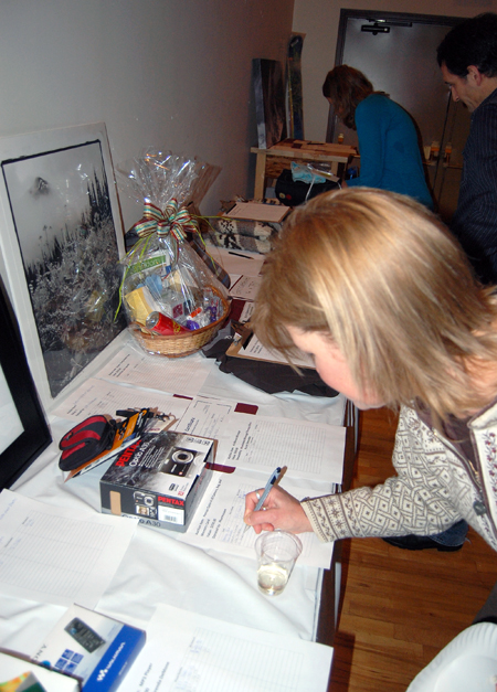 Visiting ski writer Monica Andreeff submits a bid for one of the items in the silent auction.  David F. Rooney photo