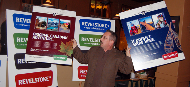 Thom Tischik, marketing manager for the Revelstoke Accommodation Association brandishes two of the campaign ads proposed for the rebranding of Revelstoke. David F. Rooney photo