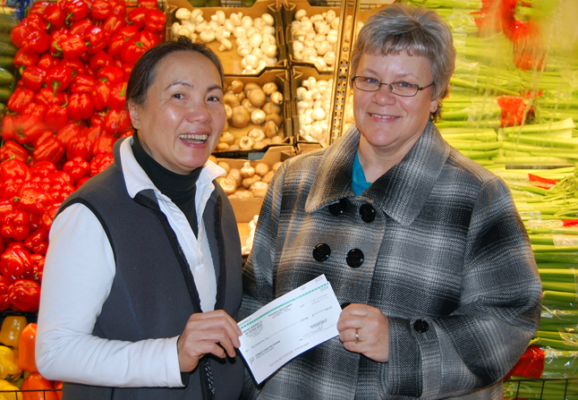"""Georgina Chin of Southside Market hands Patti Larson, Community Connections' Outreach Services Manager and Food Bank coordinator, a cheque for $953.20 collected through the supermarket's Community Giving Program that allows customers to make small donations to the Food Bank when they purchase their groceries. """"This is really very generous,"""" Larson said. David F. Rooney photo"""