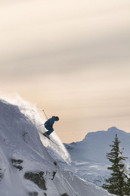 Against a peach-coloured sky a skier races through the snow at the Freeskiing Championships at RMR. Kip Wiley photo