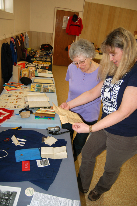 Judy Minifie (left) and Carol Fitchett examine some documents they found in an old Girl Guide uniform from the 1940s. The notes were in the name of Marth Stobart. David F. Rooney photo