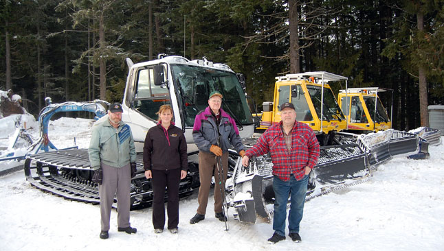 Tom Dickinson, Angie Threatful, Larry Street and Wayne Davis pose with the Snowmobile Revelstoke Society's three groomers — the new silver one which they purchased for $133,000 with the assistance of a $75,000 grant from Resort Municipality Fund — and the two old ones they maintain. The SRS is a non-profit society whose mandate is to provide the snowmobile areas of Revelstoke with groomed trails. David F. Rooney photo