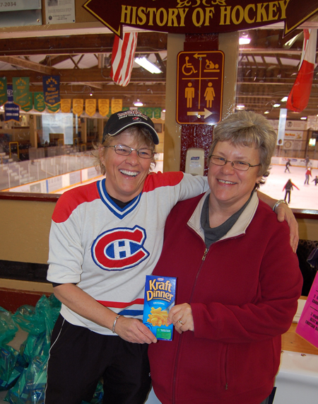 Human Hockeyville Banner organizer Suzie Cameron (left) hugs Patti Larson, outreach services manager for the Community Connections Food Bank, as they jointly hold a symbolic box of Kraft Dinner. 360 boxed of KD used in the Human Hockeyvilole Banner project at the Forum on Saturday were donated to the Food Bank. David F. Rooney photo