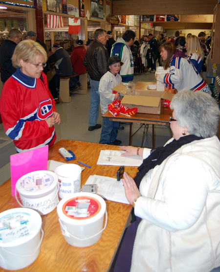 Catherine Bell of the Revelstoke Hockeyville Committee (right) talks with a supporter at the Committee's table on the concourse at the Forum. The Committee is very pleased with the level of support the big has achieved and hopes people will make one last push to file their stories before its all over — for this stage of the national competition — at midnight on Monday. David F. Rooney photo