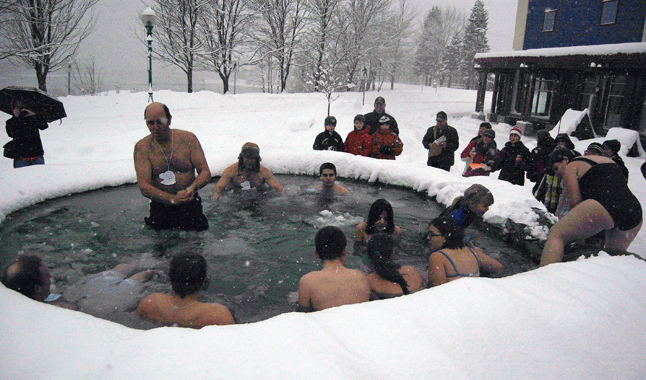 Gord Robinson stands in the water, bracing himself before immersing his body in the icy waters of the Polar Plunge Pool. The two men in back, Tony Rota (wearing the hat) and Lucas Schneble won the Longest Male Plungers category. They withstood the bine-chilling temperatures for more than 21 minutes. David F. Rooney photo