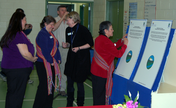 Lynne Barisoff (left), Brenda Percell and Shan Jorgenson-Adam share a light moment as they wait their turn to sign copies of the agreement. Margaret Verhaeghe, chairwoman of the SD 19 Aboriginal Enhancement Committee, was the first person to sign the agreement. The over-size documents are copies of standard 8x11 documents that they also signed. One of the large copies will be kept in the SD 19 archive and the other will be put on display at Revelstoke Secondary School. David F. Rooney photo