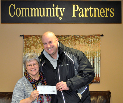 Community Connections Food Bank Manager Patti Larson was all smiles on Thursday as she accepted a $1,000 cheque from Telus Service Manager Kirk Panser. The funds will be used to help finance the Kids' Snack Program. David F. Rooney photo