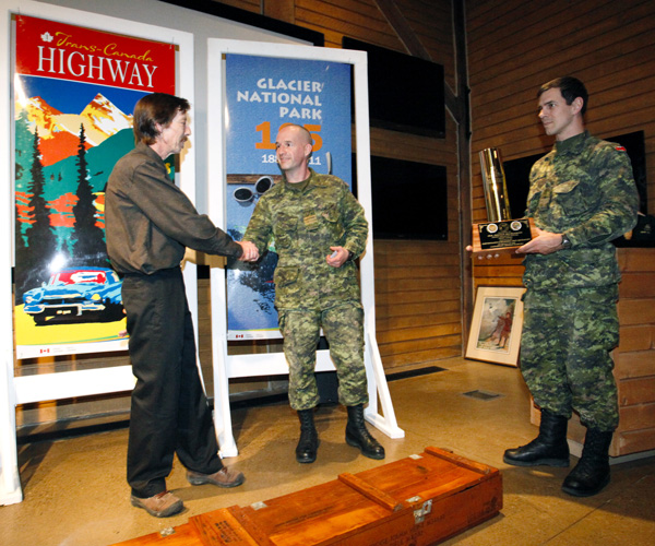 In appreciation for Bruce's years of service as a partner with the Canadian Armed Forces operating the world's largest mobile avalanche control program, Lt. Colonel Pat Quealy and Captain Patrick Levis presented him with a retirement gift featuring an engraved 105mm howitzer shell casing. Rob Buchanan photo courtesy of Parks Canada