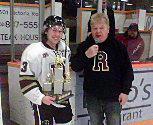 """The Grizzlies Austin Donaldson was named the Grizzlies' Fan Favourite for 2013 and presented with a trophy by team owner Lew Hendrickson during Sunday evening's game. """"Austin Donaldson epitomized the heart and soul of the Revelstoke Grizzlies this year, constantly sacrificing, scoring important goals, and being a true leader,"""" said the team's volunteer business manager, Steve Smith. Donaldson is the team's scoring leader with 65 points to his credit. The 19-year-old forward is from Calgary. This is his second season with the Grizzlies. The team won their final regular season game against the Penticton Lakers by a score of 6-2 on Sunday night. The Grizzlies are, with 58 points, currently in third place behind the first-place North Okanagan Knights and the Sicamous Eagles in the Doug Birks Division of the KIJHL's Okanagan/Shuswap Conference. Steve Smith photo courtesy of the Revelstoke Grizzlies"""