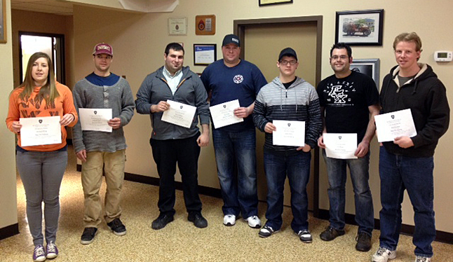 """Fire Chief Rob Girard presented 9 local firefighters with Justice Institute of BC Basic Firefighting Certificates at the February meeting night. """"Each of these firefighters have successfully completed both the written and practical portions for the certificate requirements,"""" Girard said, adding that each of them devoted """"an unbelievable amount of work time and dedication… to protecting our community."""" The program offered additional training in safety, personal protective equipment, self-contained breathing apparatus, ropes and knots, ladders, ventilation, fire hoses, water supplies and appliances and streams.  """"We are very proud of each of them and their accomplishments,"""" Girard. Here, Firefighters Elizabeth Ploeg, Christian Foster, Phil Bafaro,  Neil Schiiler, Jeremy Murray, Lyle Knapp, and Brad Goodwin pose with their certificates. Missing are Firefighters Geoff Wilson and Riley Creighton. Photo courtesy of the Revelstoke Fire Rescue Service"""
