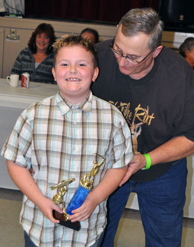 Justus Cameron beams as he receives his second-place trophy in the Junior Rainbow Category. His catch was 2 lbs 14 oz. David F. Rooney photo