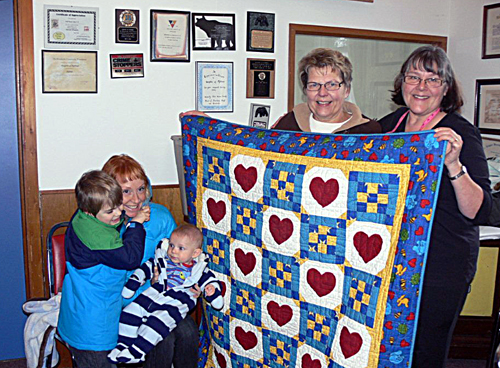 When infant Hugo Poole underwent heart surgery last month, the thoughtful and generous ladies of the Quilting Guild decided to produce a cuddly comfort quilt for him.  Named Hearts to Heart, the quilt was presented to him on February 16 during the guild's annual retreat for two days of sewing and project development at the Knights of Pythias Hall. From left to right in this photo are Hugo's big brother Baron (who also received a gift from the guild), mommy Angela Poole, baby Hugo and guild members Irene Scarcella and Linda Walford of Cherry Blossom Lane Quilting. Photo courtesy of Quilting Guild member Darlene Dabell