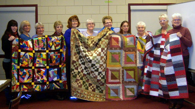 """Members of the Quilters' Guild presented the Revelstoke Hospice Society with a set of quilts they made """"for Palliative Care individuals that we support,"""" Hospice President Vivian Mitchell said in an e-mail to The Current.  The people in the picture are, from left to right:  Hospice volunteer Sarah Darval, Sharon Cain and Marie March from the Quilter's Guild, Hospice volunteer Jill Holloway, Quilters Darlene Dabell and Irene Scarcella, Hospice volunteer Phyllis Floyd, Quilters Sheila Crowe, Mary Bradshaw and Diane Frost, and Mitchell herself. """"The Revelstoke Hospice Society appreciates the support and community partnership with the Mount Revelstoke Quilters' Guild and thanks them immensely,"""" Mitchell said. The presentation was made at the conclusion of an end-of-life workshop last Wednesday. Darlene Dabell photo courtesy of the Revelstoke Hospice Society"""
