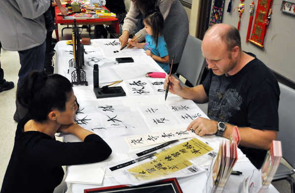 Jim Smith (right) demonstrate's calligraphic technique to an fascinated Susy Huang at the English as a Second Language booth. David F. Rooney photo