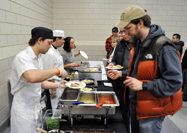Matt Shaw (;eft) serves up a tasty plate of perogies at the Buns & Beyond food booth. David F. Rooney photo