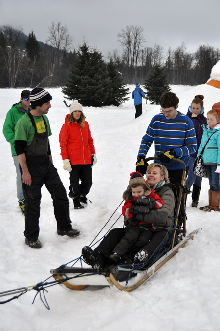Professional dog sledder Eric Marsden (left) chats with Emma Kirkland as she hugs her nephew. Emma was quite excited to take the boy for a sled ride. David F. Rooney photo