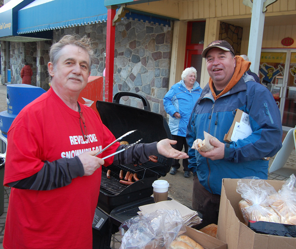 Dennis Berarducci hands Gary Starling a hot dog at the food stand organized by the Revelstoke Snowmobile Society. David F. Rooney photo