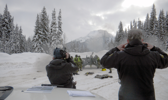 Observers plug their ears as a howitzer fires a round during Operation Palaci, the Canadian Armed Forces (CAF) contribution to avalanche control in British Columbia. This avalanche-control operation has concluded after another successful season. Jacolyn Daniluck photo courtesy of Parks Canada