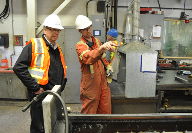 One of Downie's workers explains is job to Doug Clovechok. Despite full employment, it is sometimes difficult to find trained workers — even truck drivers. David F. Rooney photo