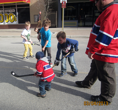 """Rusty Berarducci watches over his two-year-old son AJ (front left) as he plays hockey with """"the big boys"""" while waiting to learn if grandfather was going to be a big winner. Photo by Laurie Berarducci"""