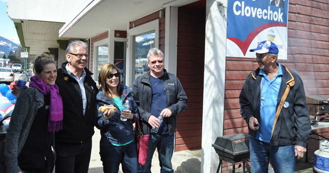 BC Liberal Doug Clovechok and his supporters held a barbeque at their campaign office at noon on Sunday. Here, Doug poses with well-wishers and passersby who stopped to joy a burger. David F. Rooney photo