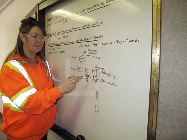 Deanne Stephenson, manager of the semi-automated Cascades plant in Kelowna, draws a diagram showing the layout of the plant where consumer recyclables are sorted. Laura Stovel photo